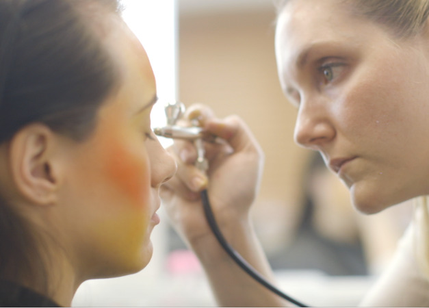 student applying airbrush make-up
