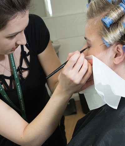 An Iver Academy student applying theatre makeup to a model