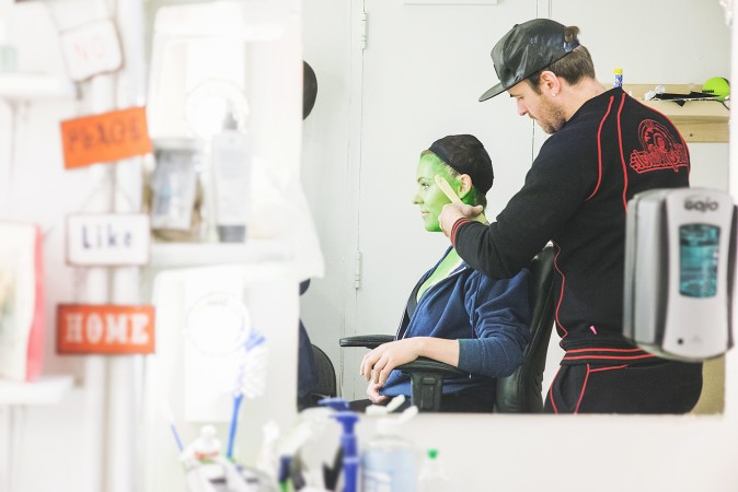 A theatre make-up artist applying green makeup to transform an actress into Elphaba in Wicked