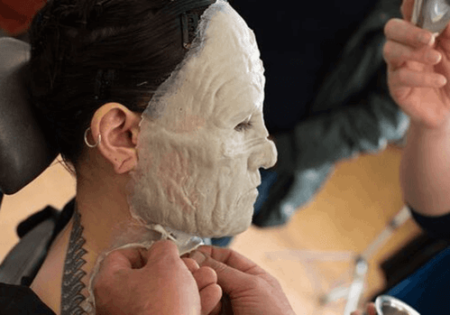 A prosthetic make-up piece being applied to a model